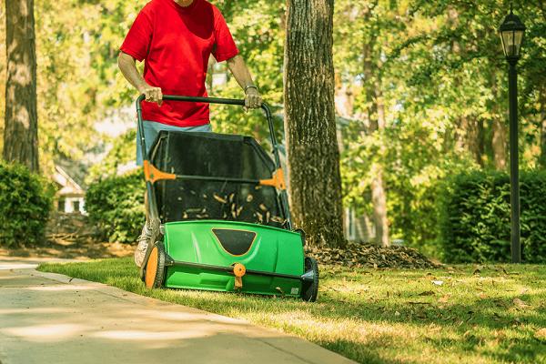 Man-using-manual-lawn-sweeper