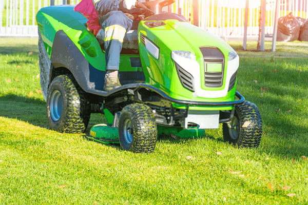 lawn-mower-with-driver-mowing-the-grass-on-a-green-meadow